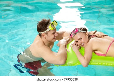 Image of pretty girl looking at camera in swimming pool with her boyfriend near by