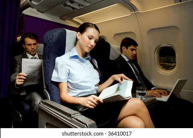 Image of pretty girl reading magazine while handsome man typing next to her in airplane