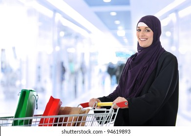 Image of pretty muslim woman with cart looking at camera and smiling