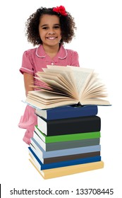 Image of pretty schoolgirl reading textbook near pile of books.
