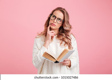 Image of pretty thinking lady reading book over pink background. Looking aside.