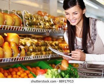 Image of pretty woman choosing products in supermarket with list of things to buy