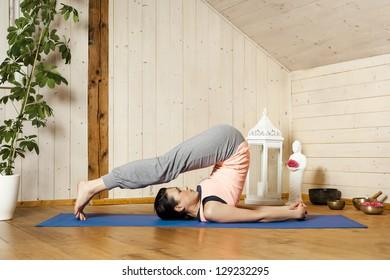 An image of a pretty woman doing yoga at home - Halasana