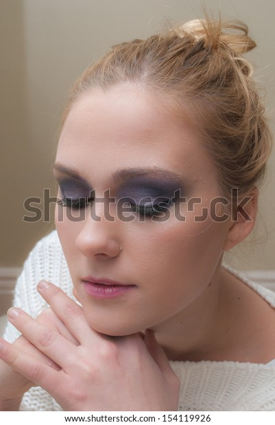 An Image of a pretty woman in her twenties with dramatic eye make-up