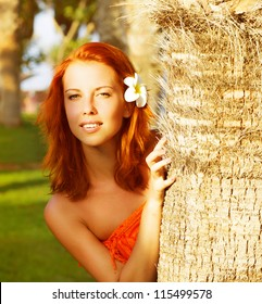Image of pretty woman look out from behind a palm tree, closeup portrait of cute girl with frangipani flower in red hair, beautiful tropical nature, luxury spa resort, holiday and vacation concept