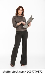 Image of pretty woman standing isolated over white background looking camera holding clipboard folder.