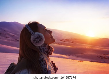Image of pretty woman walking in snowy mountains, side view of cute girl looking up, closeup portrait of female wearing warm winter earmuff, red sunset, wintertime sports, trekking and hiking concept