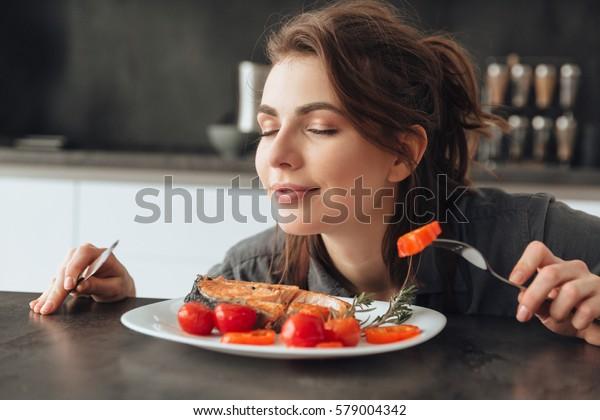 Image d'une jolie jeune femme assise dans la cuisine en mangeant et sentant le poisson et les tomates. Les yeux fermés.