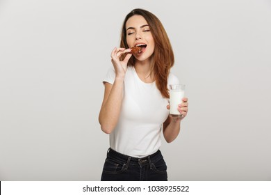 Image of pretty young woman standing isolated over grey wall background eating cookie drinking milk.