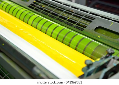 Image of process yellow ink in the fountains and on the rollers of a offset color printing press.