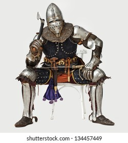 Image of proudly knight who is sitting on the chair and holding his hatchet