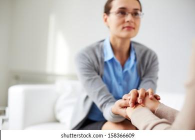 Image of psychiatrist holding hands of her patient