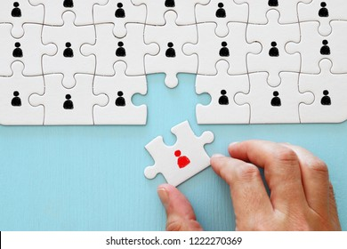 image of puzzle with people icons over wooden table ,human resources and management concept