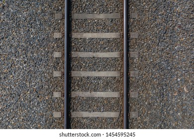 image of railway rails with sleepers on gravel close-up top view