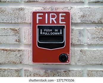 Image of an red  emergency notifier fire alarm hanging on the wall in the modern office building. Selective focus.