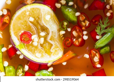 image of red and green Chilies and a freshly cut half lemon in a cup of fish Sauce, Thai people usually eat with  a spicy food