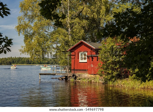 Image of red holiday cabin by a lake. Sweden.