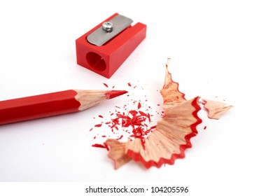 Image of red pencil, shaving and sharpener on white paper