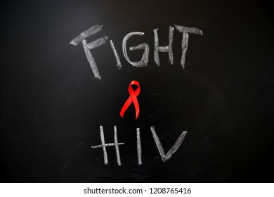 Image of red ribbon with text of fight HIV on the chalkboard