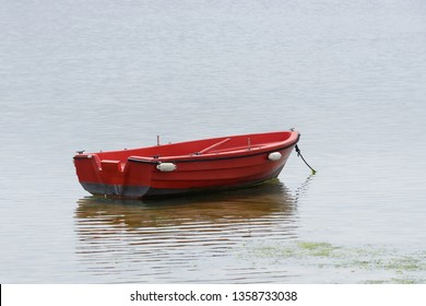 image of red wooden fishing boat moored on the shore