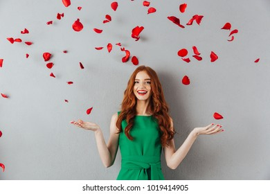 Image of redhead young happy lady in green dress standing over grey wall background over petals of roses looking camera.
