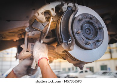 Image of replacing a new brake pad, held by a car mechanic who is about to change the new brake pads, cars in the car center