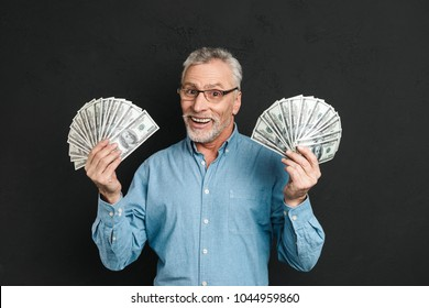 Image of rich happy adult man 60s with gray hair holding money two fans of 100 dollar bills and rejoicing his wealth isolated over black background