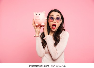 Image of rich woman 20s with long dark hair posing in girlish glasses and holding piggy bank with money isolated over pink background