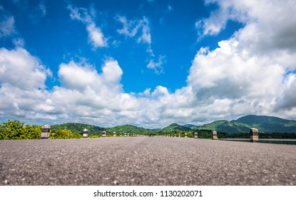 image of road and mountain line at the end with blue sky in background.