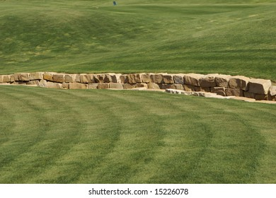 An image of a rock wall in a golf course