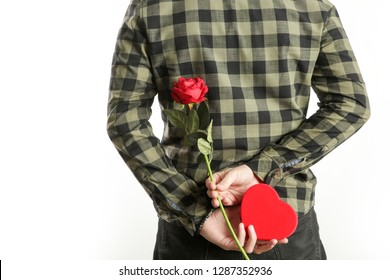 Image of the romantic guy holding a red rose and heart-shaped box behind his back