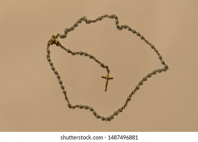 The image of a rosary or Catholic third and a crucifix pendant at its end. Religious artifact of the Catholic faith. A symbol of faith and religiosity. Crucifix of Jesus Christ.