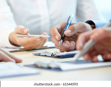 Image of row of people hands writing on papers at seminar
