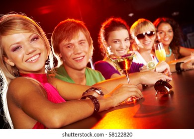 Image of row of smiling teens with pretty girl in front in the nightclub