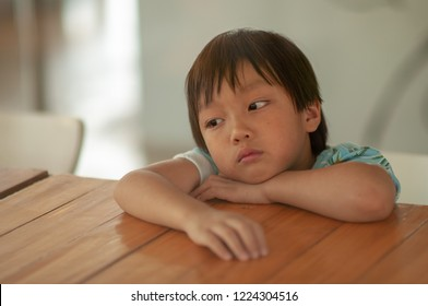 Image of sad Absenting-minded boy looking through glass in vintage color tone. Asian little kid dismal of Emotional face on wooden table. Depression in children concept.