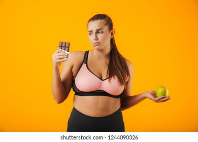 Image of sad chubby woman in tracksuit holding chocolate bar and apple in both hands isolated over yellow background