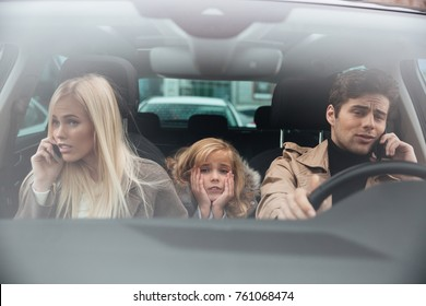 Image of sad little girl sitting in car while her mother and father talking by mobile phones. Looking camera.