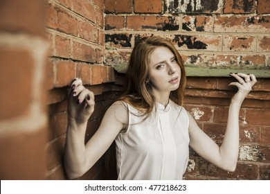 Image of a sad unhappy redhead girl in angle red brick wall. Harsh lighting for more dramatic effect. idea of the impasse, stalemate