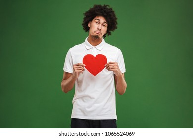 Image of sad young african curly man isolated over green wall background holding heart.