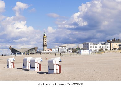 Image of sandy beach of Warnemunde with beach chairs and Lighthouse, Germany