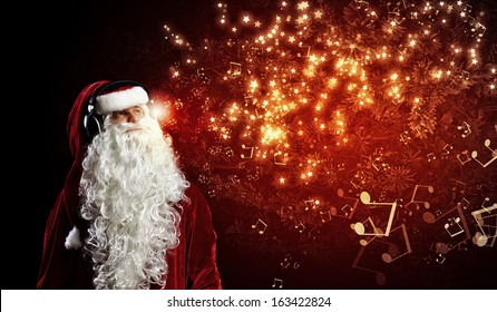 Image of Santa Claus in red costume wearing earphones