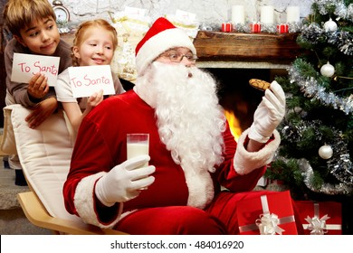 An image of Santa Claus sitting in armchair at the Christmas tree and eating cookie with milk and two children behind him