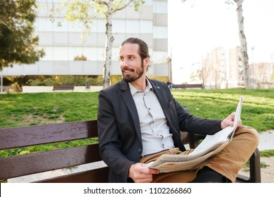 Image of satisfied attractive man 30s in businesslike suit looking aside while sitting on bench in green park and reading newspaper during sunny day