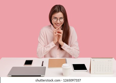Image of satisfied European lady office worker being real perfectionist, keeps hands together, smiles gently, has intention to do something intriguing, poses at desktop with modern electronic gadgets
