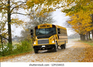 Image of school bus on the road with autumn trees and dried leaves