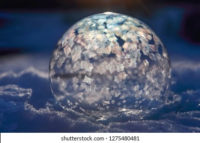 Image in a science experiment series of frozen bubble with ice crystals, ice crystals just starting to fill bubble, shallow focus