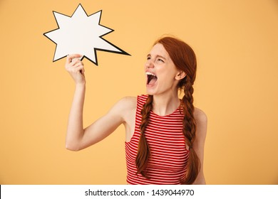 Image of a screaming displeased stressed young beautiful redhead woman posing isolated over yellow background holding speech bubble.
