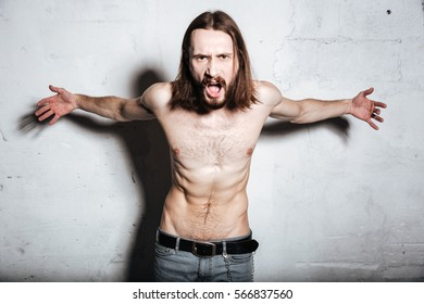 Image of screaming emotional young bearded hipster man posing isolated over wall background.