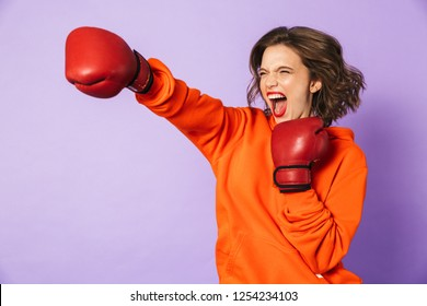 Image of a screaming strong young woman boxer posing isolated over purple background wall wearing boxing gloves.