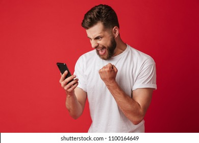 Image of screaming young man standing isolated over red wall background using mobile phone make winner gesture.